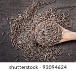 Indian cumin seeds in a spoon on table - stock photo
