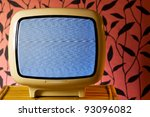 Retro grunge tv against wallpaper wall. White noise on television. - stock photo
