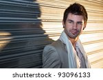 Young, handsome man casually leaning against the wall. - stock photo
