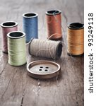 Many bobbin of thread with needle and button on table - stock photo