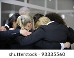 Team building event: businessmen in 'group hug' in office - stock photo