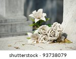 old white fake flower on grave - stock photo