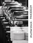 Many buffet trays ready for service in black and white. - stock photo