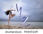 young professional gymnast woman dance with ribbon - outdoor sand beach - stock photo