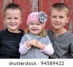 happy siblings by old barn - stock photo