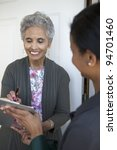 Black senior woman signs a petition at her front door - stock photo