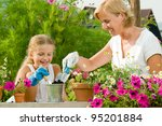 Gardening, planting - mother with daughter planting flowers into the flowerpot - stock photo