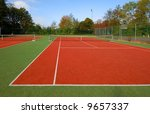 tennis court under blue sky, with autumn trees on the side. - stock photo