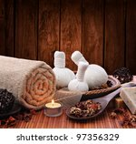 Spa massage setting with thai herbal compress stamps and candlelight - stock photo