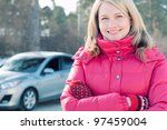 Happy female car owner standing in front of her automobile, smiling and looking at camera - stock photo