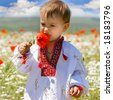 baby boy in traditional clothes in flowers - stock photo