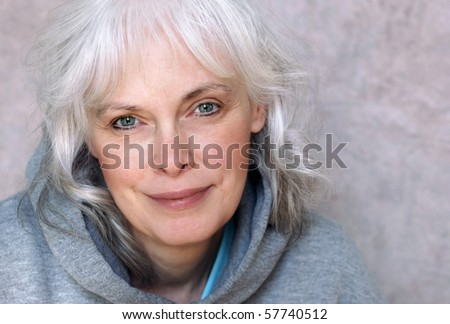 Casual portrait of happy mature woman with natural white hair and minimal ...