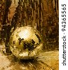 Golden disco mirror ball reflect light on glitter canvas background - stock photo