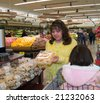 Native American woman reading labeling on a confection package in a grocery store - stock photo